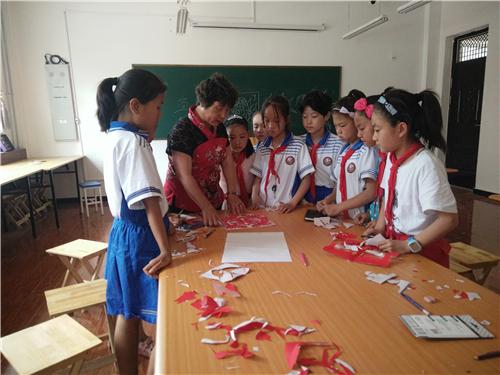 李志梅教小学生学剪纸